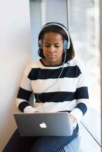 woman listening through headphones using macbook